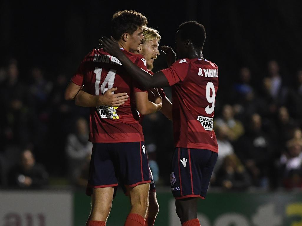 (L-R) George Blackwood, Benjamin Halloran and Papa Babacar Diawara of United react after Halloran scored a goal during the FFA Cup semi-final between the Bentleigh Greens SC and Adelaide United at Kingston Heath Soccer Complex in Melbourne, Friday, October 5, 2018. (AAP Image/Julian Smith) NO ARCHIVING, EDITORIAL USE ONLY