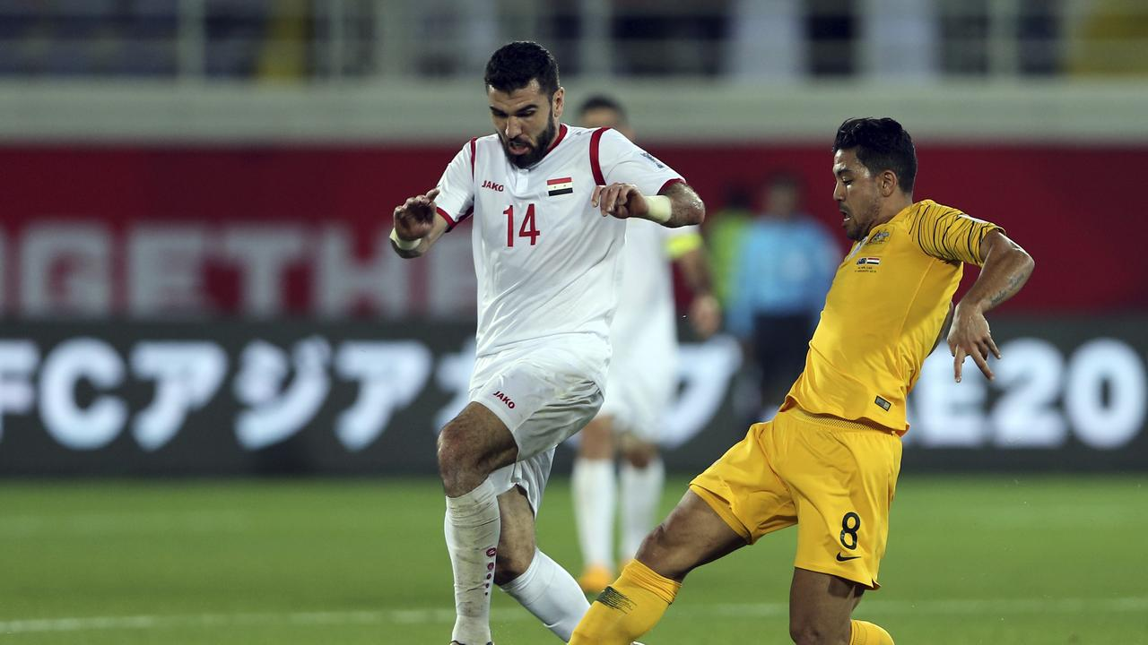 Syria's midfielder Tamer Haj Mohamad, left, duels for the ball with Australia's midfielder Massimo Luongo