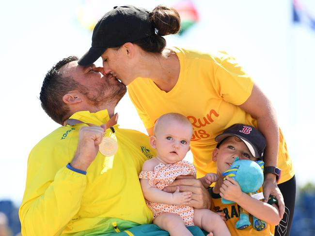 Kurt Fearnley plants a kiss on wife Sheridan with son Harry and daughter Emilia during the medal ceremony following his gold medal performance. Picture: Getty Images