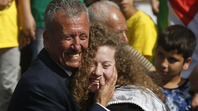 Ahed Tamimi is hugged by her father Bassem during a press conference on the outskirts of the West Bank village of Nabi Saleh near the West Bank city of Ramallah. Picture: AFP/Majdi Mohammed