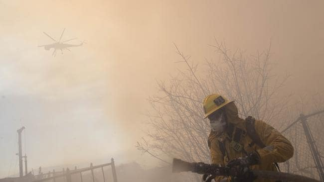 A firefighter carries a hose during work to protect homes from the flames of a wildfire in the Pacific Palisades area of Los Angeles. AP Photo: Christian Monterrosa