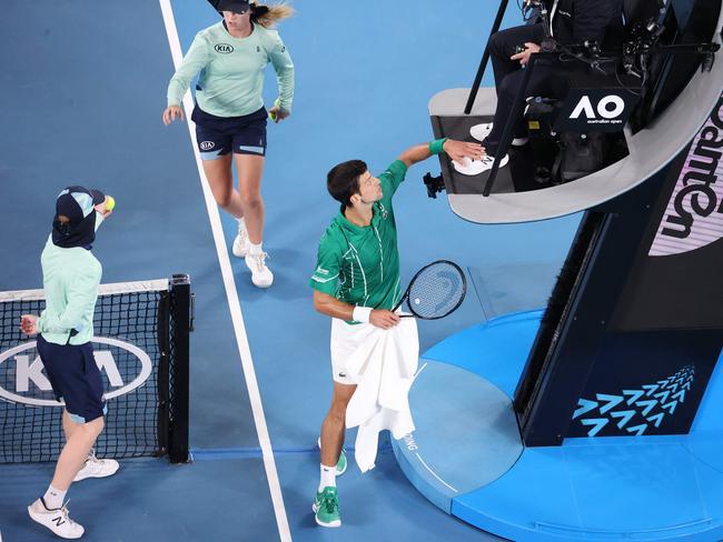 Serbia's Novak Djokovic pats the feet of the umpire. (Photo by DAVID GRAY / AFP)