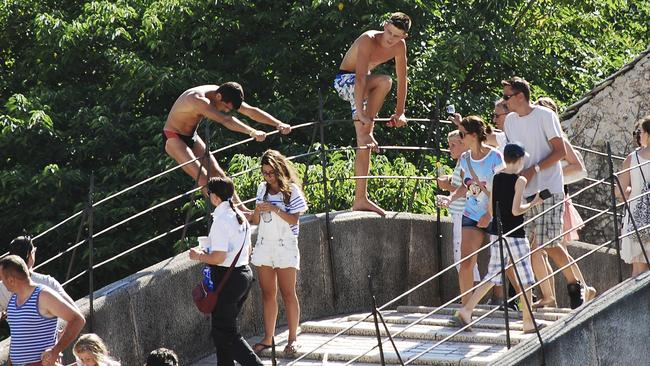 Two young men attempt to collect money from tourists interested in jumping off the Stari Most bridge in Mostar.
