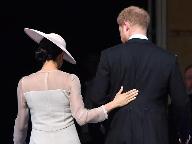 Meghan places a protective hand on Harry's back. Picture: Dominic Lipinski