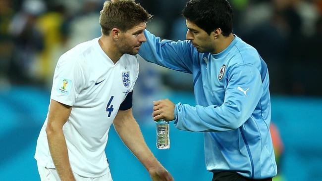 Luis Suarez puts an arm around his club teammate.