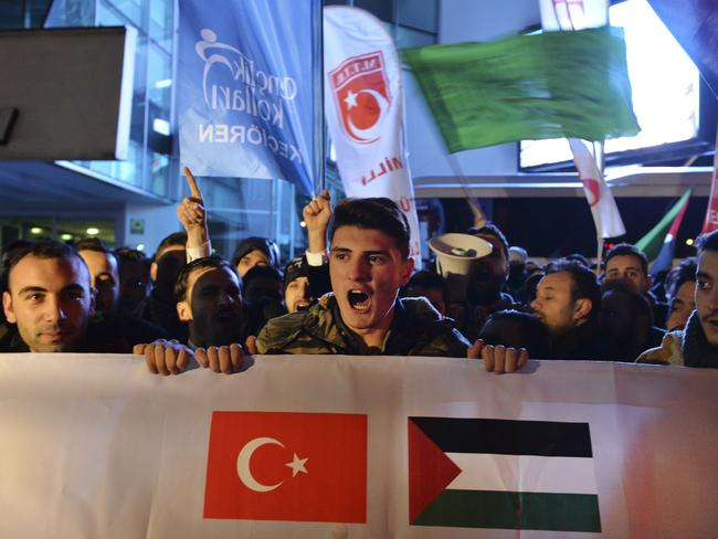 Holding a banner with a Turkish and a Palestinian flag, protesters chant anti-American slogans during a demonstration near the US embassy in Ankara, Turkey. Picture: AP Photo