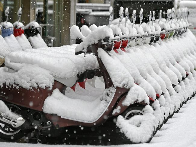 Vespa scooters are covered with snow in Zurich, Switzerland after the Alp region was hit by heavy snowfall. Picture: AP