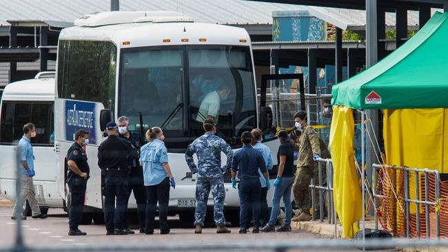 Government agencies gather near buses taking cruise ship passengers to the Howard Springs quarantine facility. Picture: AAP/Helen Orr