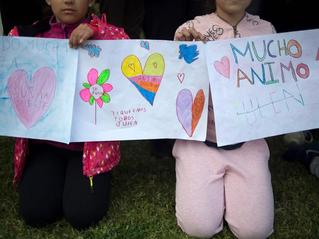 Two girls hold drawings bearing hearts and messages of support for the little boy. Picture: AFP