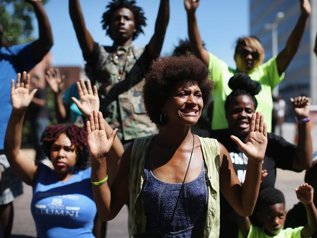 """Sign language ... Demonstrators raise their hands and chant """"hands up, don't shoot"""" during a protest over the killing of Michael Brown in Clayton, Missouri. Some reports state that Brown had his hands in the air when he was shot and killed by a police officer. Source: AFP"""