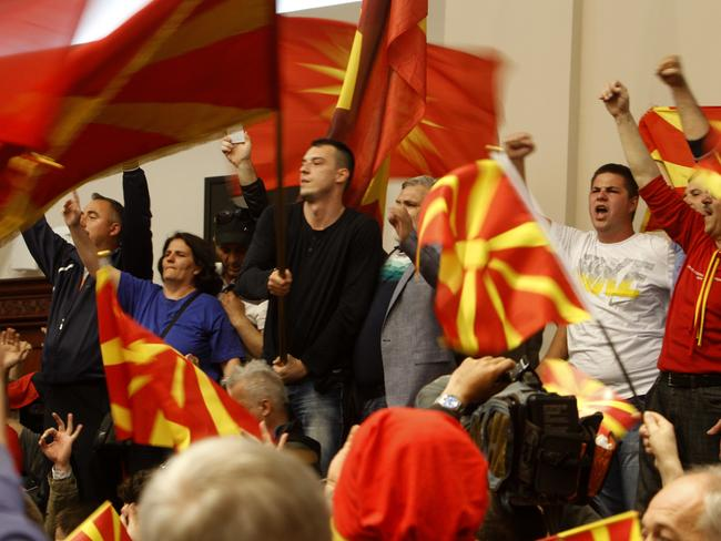 Protesters wave national flags after entering into the parliament building.