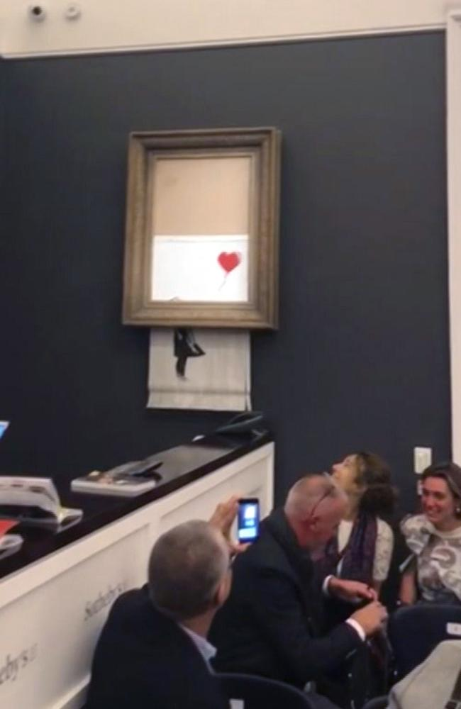 People watch as the Banksy artwork is shredded at Sotheby's. Picture: Pierre Koukjian via AP