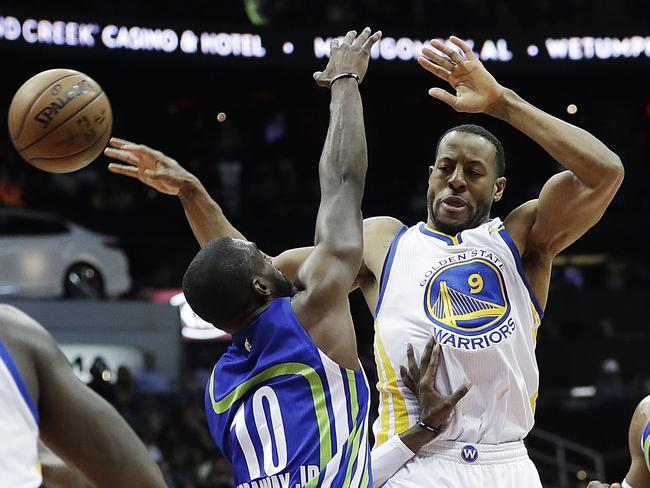 Golden State Warriors' Andre Iguodala, right, passes the ball against the defence of Atlanta Hawks' Tim Hardaway Jr.