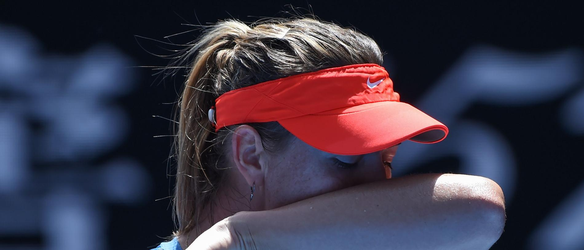 Russia's Maria Sharapova wipes sweat off her face while playing against Australia's Ashleigh Barty during their women's singles match on day seven of the Australian Open tennis tournament in Melbourne on January 20, 2019. (Photo by Greg Wood / AFP) / -- IMAGE RESTRICTED TO EDITORIAL USE - STRICTLY NO COMMERCIAL USE --