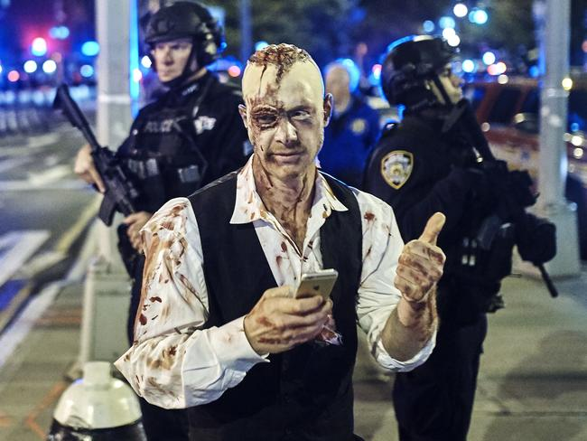 A reveler gets his picture taken by a friend in front of heavily armed police during the Greenwich Village Halloween Parade. Picture: AP