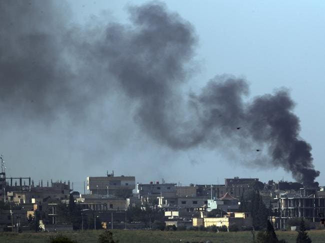 Smoke billows from targets in Tel Abyad, Syria, during bombardment by Turkish forces on Friday. Picture: Lefteris Pitarakis.