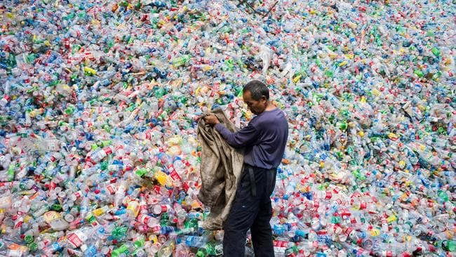 A Chinese labourer sorting out plastic bottles for recycling in Dong Xiao Kou village, on the outskirts of Beijing. Picture: Fred Dufour/AFP