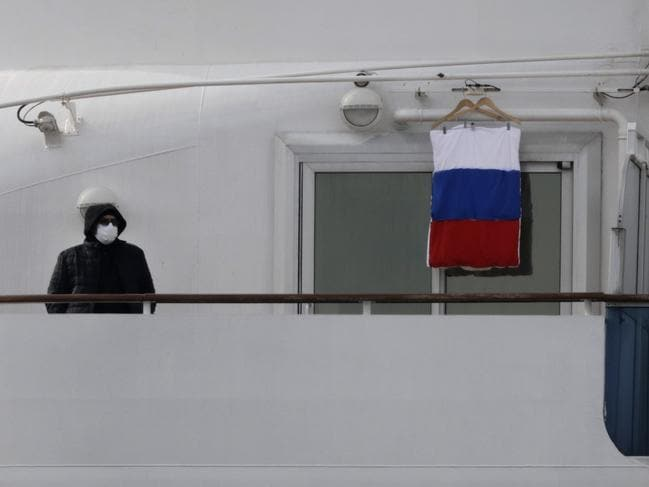 A quarantined passenger on the Diamond Princess cruise ship stands on the balcony of his cabin next to a Russian flag on Saturday. Picture: Jae C. Hong