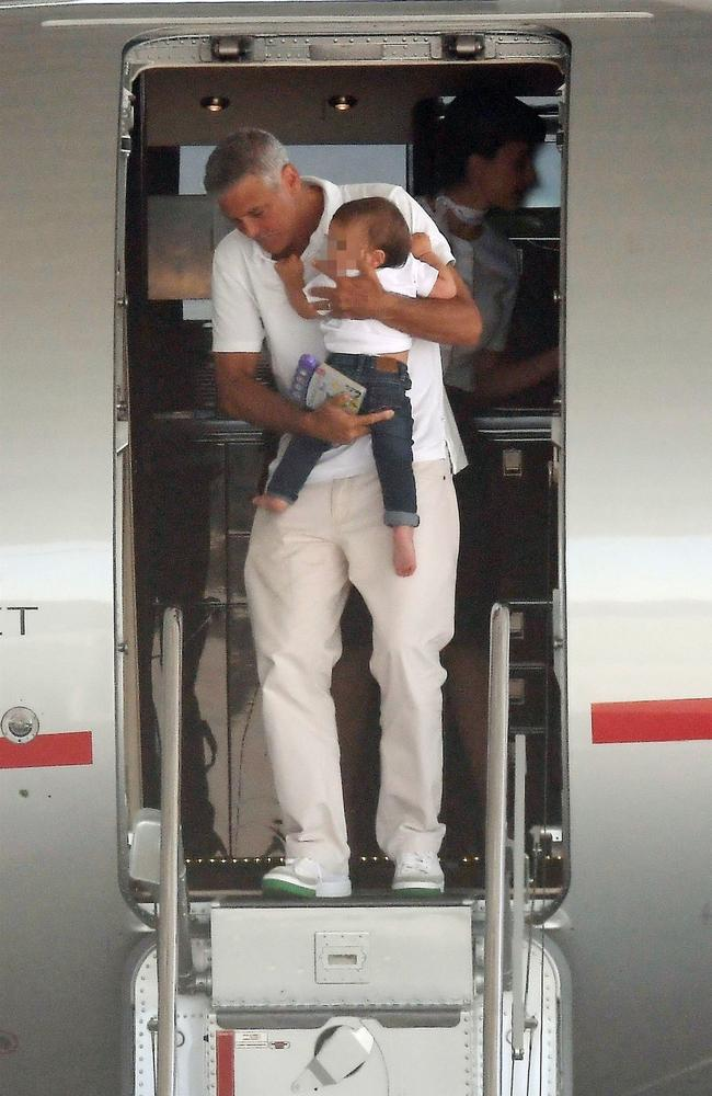 George cradled his son Alexander as he got off the private plane first. Picture: BACKGRID