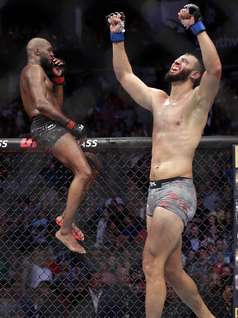 Jon Jones, left, sits on the fence as Dominick Reyes, right, celebrates.