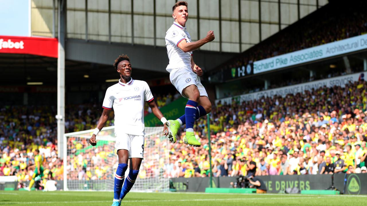 Mason Mount leaps in the air in front of Tammy Abraham after scoring.