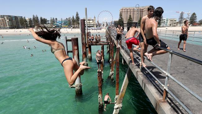 People jump off the Glenelg jetty on Monday. Temperatures are predicted to reach near-record levels this week. Picture: AAP / Kelly Barnes