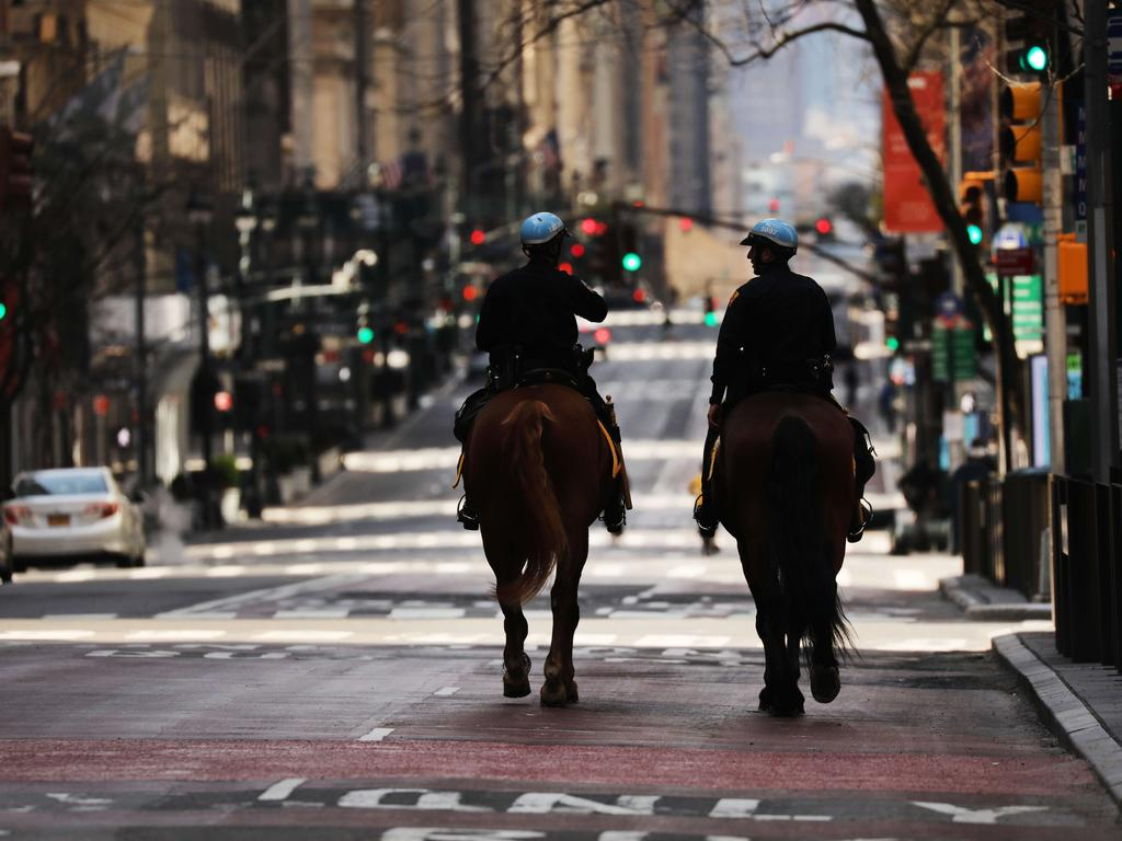 Police officers ride horses on the quiet Fifth Ave in New York. Image: / Getty Images / AFP