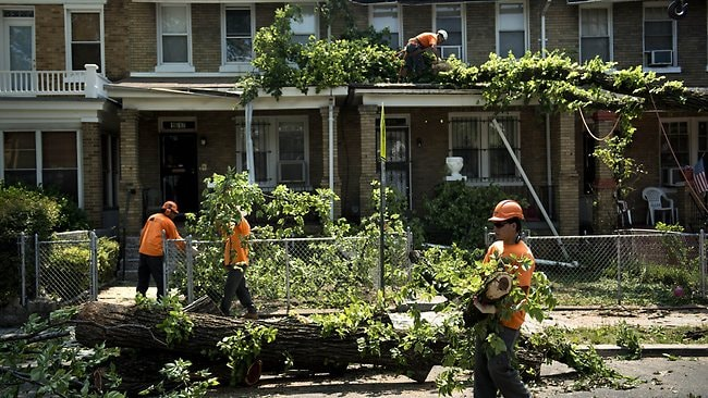 A crew clears a fallen tree felled by strong winds from a row of homes in Washington, DC after power cuts caused by a record breaking heatwave in the eastern USA. Pictures: AFP