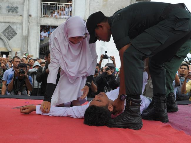 The man collapsed as he was getting caned by a religious officer. Picture: Chaideer Mahyuddin/AFP
