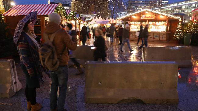 People pass by concrete security barriers at the 2017 opening day of the Christmas market. Picture: Sean Gallup/Getty
