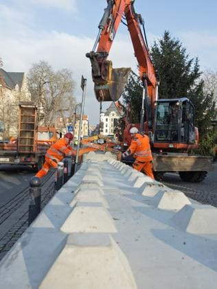 Workers set concrete barriers at the Christmas market in Erfurt. Picture: Jens Meyer/AP Photo