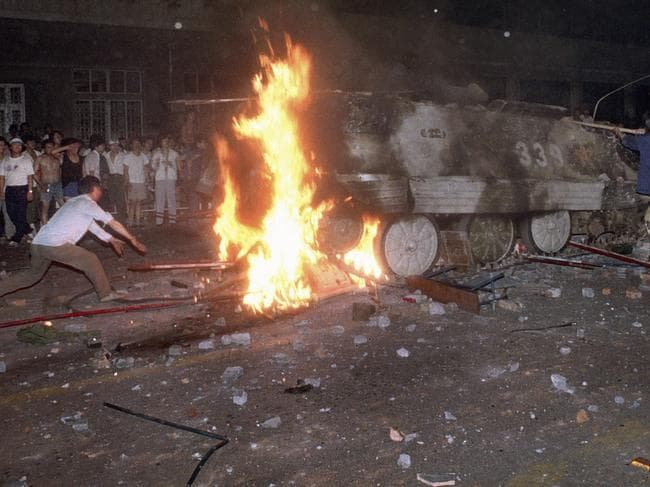 In this early June 4, 1989 file photo, a student protester puts barricades in the path of an already burning armored personnel carrier that rammed through student lines during an army attack on pro-democracy protesters on Beijing's Tiananmen Square. Picture: Jeff Widener/AP