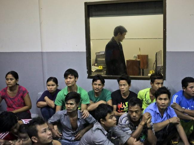 Burmese workers sit on the floor as a member of Thailand's Department of Special Investigation searches the office of a shrimp shed during a November 9 raid in Samut Sakhon, Thailand. Picture: Dita Alangkara
