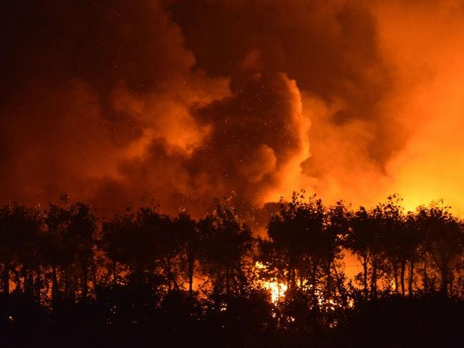 Burning ... Fire and smoke rise from the site of a series of explosions in Tianjin. Picture: AFP
