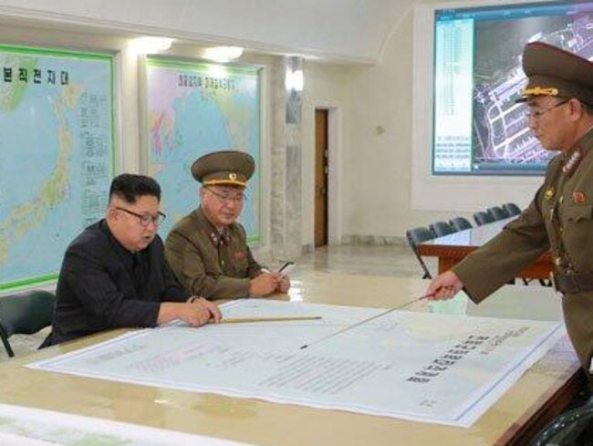 North Korean leader Kim Jong-un is presented with plans to launch ballistic missiles towards the US territory of Guam. The map in front of him details the flight path of a missile from North Korea towards the strategically significant Pacific island. Picture: KCNA