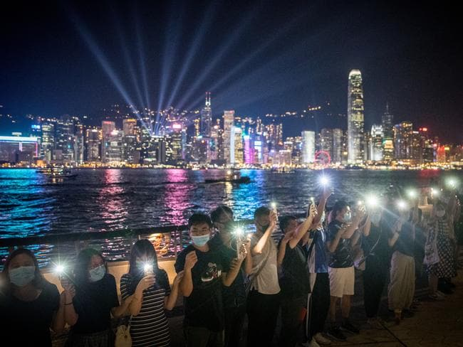 Protesters wave their phones along Victoria Harbour. Picture: Chris McGrath/ Getty Images