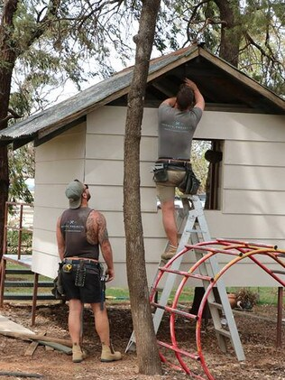 Volunteers tackle some repairs at a children's play area.