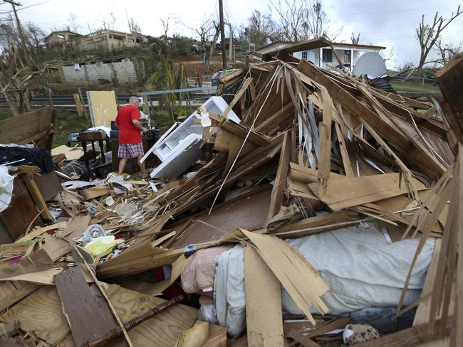 Jose Garcia Vicente walks through rubble of his destroyed home in the aftermath of Hurricane Maria, in Aibonito, Puerto Rico. Picture: Gerald Herbert