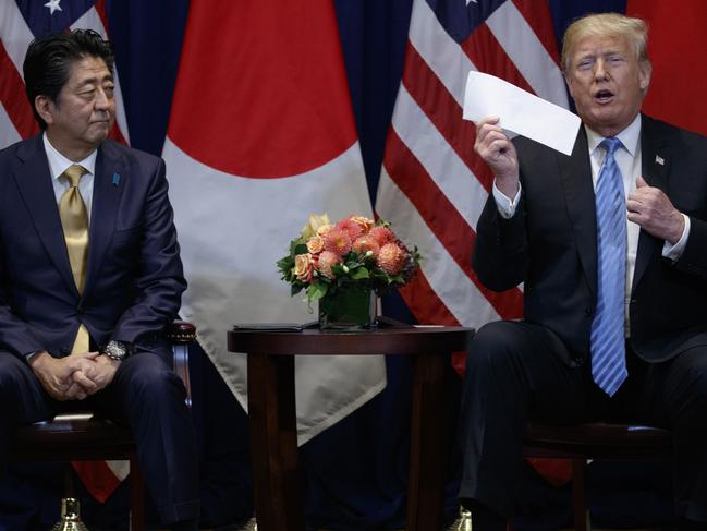 US President Donald Trump takes a letter from North Korean leader Kim Jong-un from his suit coat pocket during a meeting with Japanese Prime Minister Shinzo Abe during the United Nations General Assembly, Wednesday, Sept. 26, 2018, in New York. Picture: AP Photo/Evan Vucci