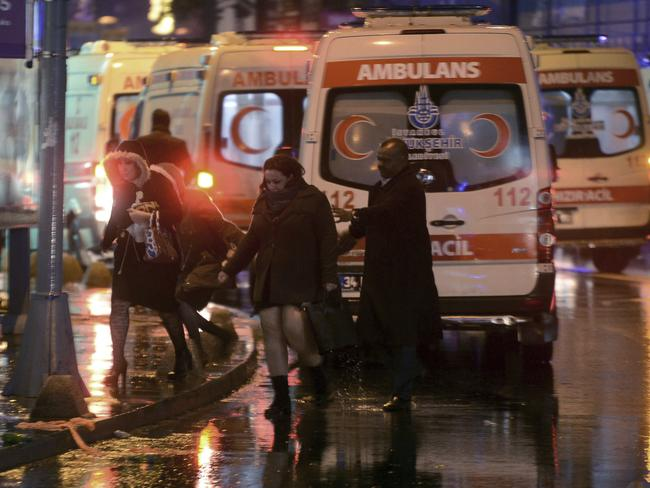 People leave as medics and security officials work at the scene. Picture: IHA via AP