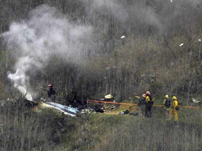 Firefighters attend the charred wreckage.