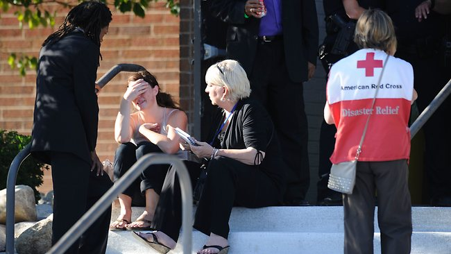 A distraught woman is counseled by a pastor and an unidentified advocate in front of Gateway High School in Aurora, Colorado where the families of the missing are meeting following the shooting at the Century 16 movie theater. Picture: AFP / JONATHAN CASTNER