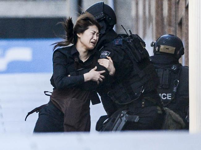 Another one of the hostages falls into the arms of a police officer after escaping the Lindt Cafe in Martin Place. Picture: Chris McKeen