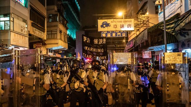 \Police hold up a warning banner as they charge on a street to disperse protesters during a demonstration on Hungry Ghost Festival day in Sham Shui Po district on August 14, 2019 in Hong Kong, China. Picture: Anthony Kwan/Getty Images