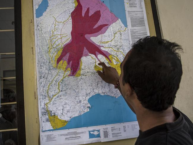 A man looks a map of the danger zones at the mount Agung monitoring station. Picture: Ulet Ifansasti/Getty Images