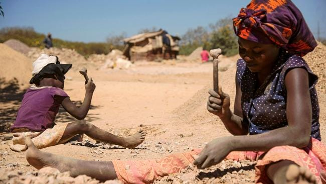 A child and a woman break rocks extracted from a cobalt mine at a copper quarry and cobalt pit in the DRC. Picture: Junior Kannah / AFP