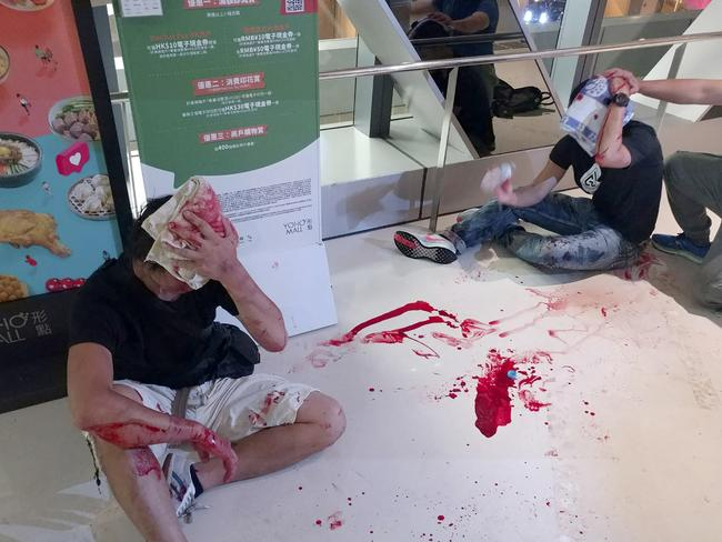 Two men in black shirts cover their heads as they bleed in a Hong Kong train station. Picture: Apple Daily/AP