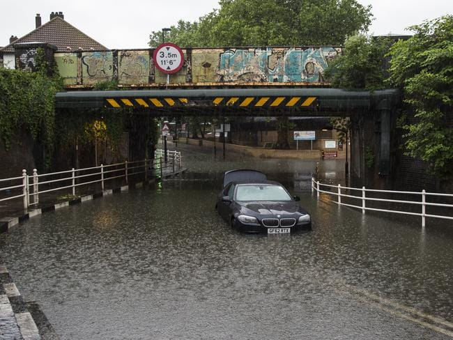 A car is abandoned under a bridge in Battersea, London, after getting stuck in floodwater following overnight thunderstorms in the south of England.