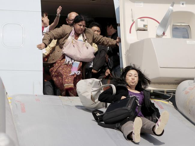 Passengers being evacuated from a Cathay Pacific Boeing 747 aircraft — complete with luggage. Picture: AFP