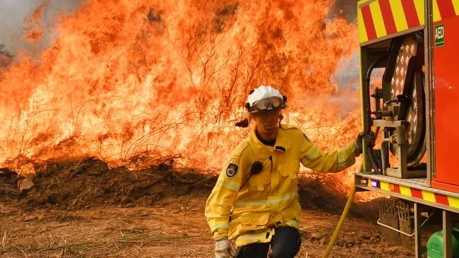 New South Wales Rural Fire Service firefighters are seen back burning and fighting fires on Long Gully Road in the northern New South Wales town of Drake. Picture: AAP/Darren England